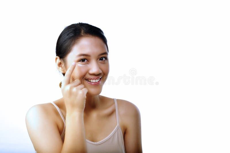 Jolie femme mettant sur la crème d'oeil photo libre de droits