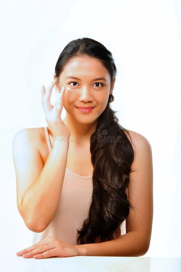 Jolie femme mettant sur la crème d'oeil photos stock