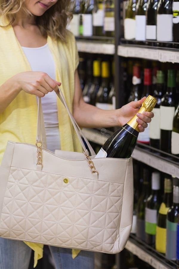 Download Jolie Femme Mettant Une Bouteille De Champagne Dans Son Sac Photo stock - Image du propriétaire, activités: 56488118