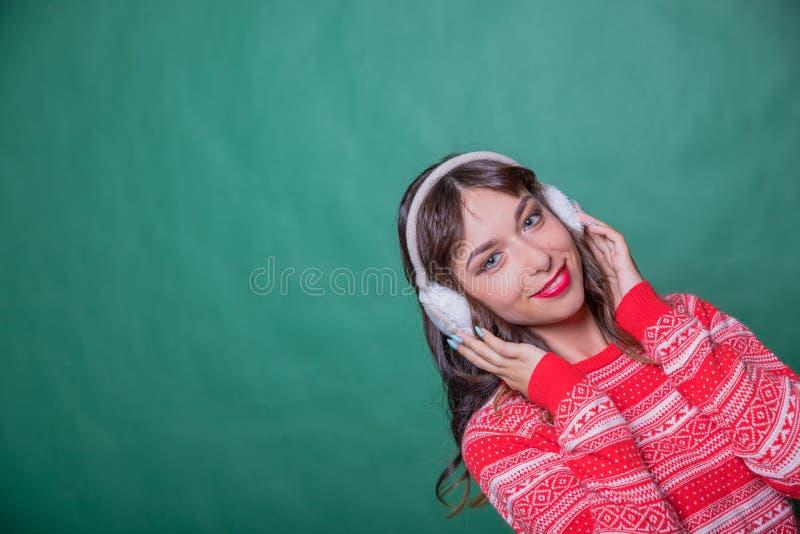 Jolie femme mignonne de sourire d'isolement Fille attirante dans les bouche-oreilles et le pull rouge de chandail de Noël Mode d' photos libres de droits