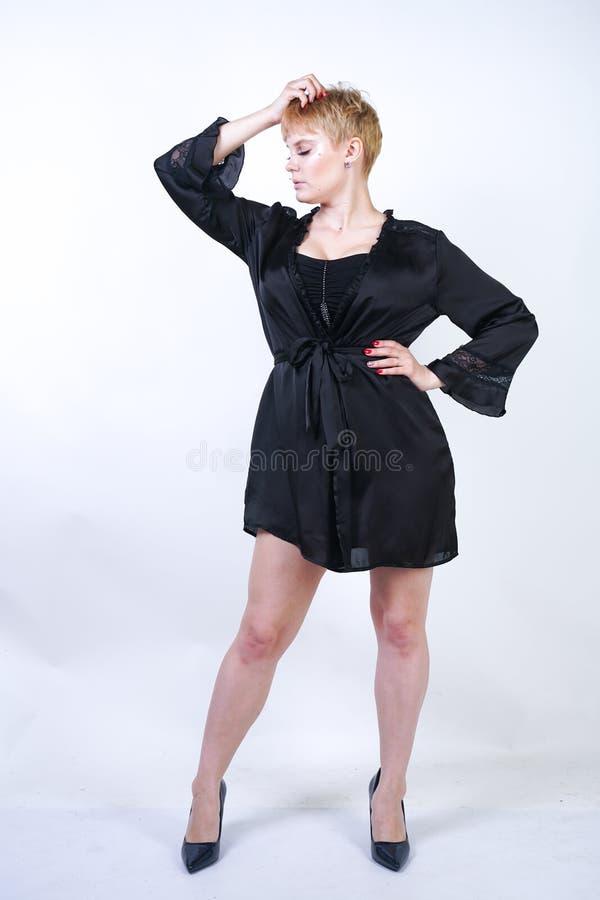 Jolie femme plus de taille avec les cheveux courts et corps sinueux potelé utilisant de rétros sous-vêtements de combinaison et p photographie stock