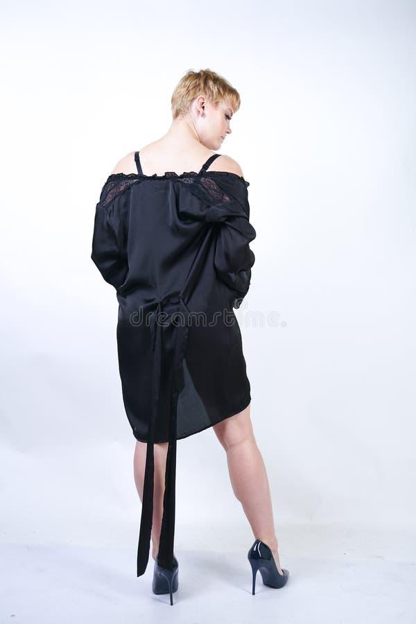Jolie femme plus de taille avec les cheveux courts et corps sinueux potelé utilisant de rétros sous-vêtements de combinaison et p photographie stock libre de droits