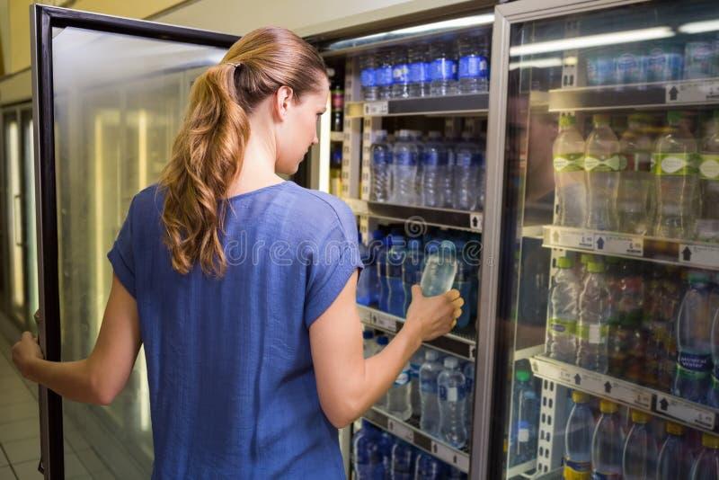 Download Jolie Femme Prenant La Bouteille De L'eau Dans Le Réfrigérateur Image stock - Image du : 56488419