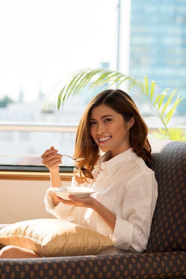 Jolie femme prenant le petit déjeuner photo stock