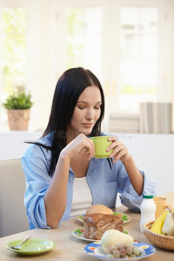 Jolie femme prenant le petit déjeuner images stock