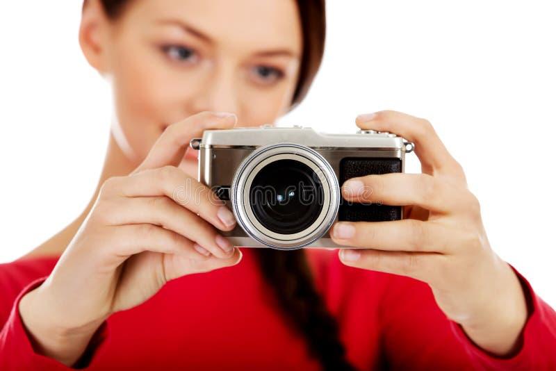 Jolie femme prenant une photo utilisant l'appareil-photo classique de slr images stock
