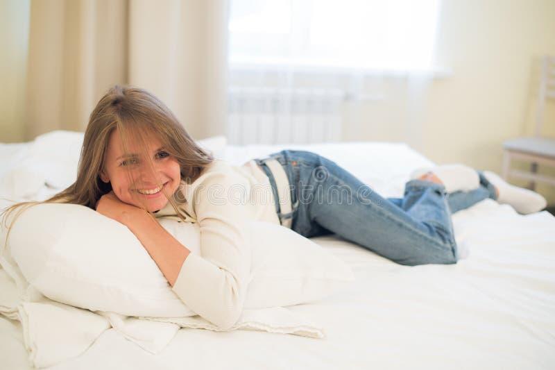 Jolie femme réfléchie de sourire se situant dans le lit à la maison photos stock