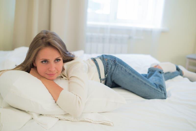 Jolie femme réfléchie de sourire se situant dans le lit à la maison photo libre de droits