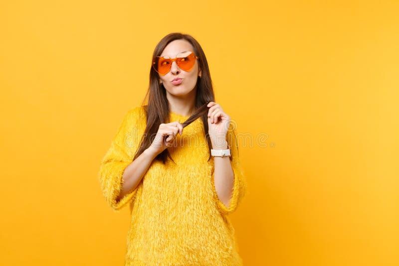 Jolie femme rêveuse dans le chandail de fourrure, verres oranges de coeur recherchant pensants, rêvant jugeant des cheveux d'isol photographie stock