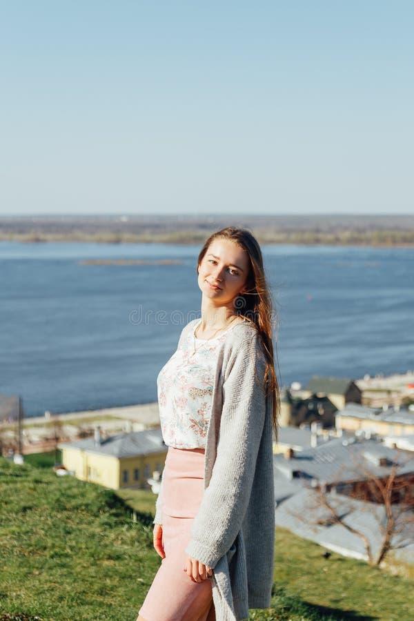Jolie femme rêveuse s'asseyant par la rivière de ville image stock