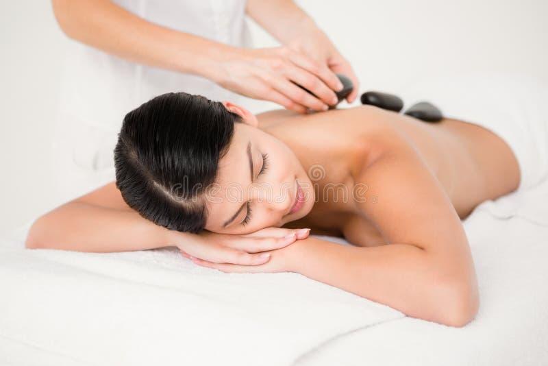 Jolie femme recevant un massage en pierre chaud image stock