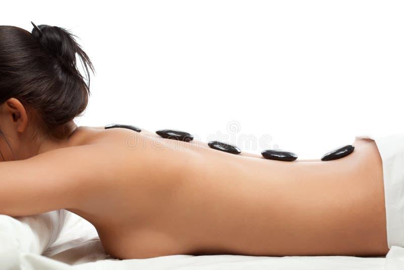 Jolie femme recevant une thérapie avec les pierres chaudes photo libre de droits