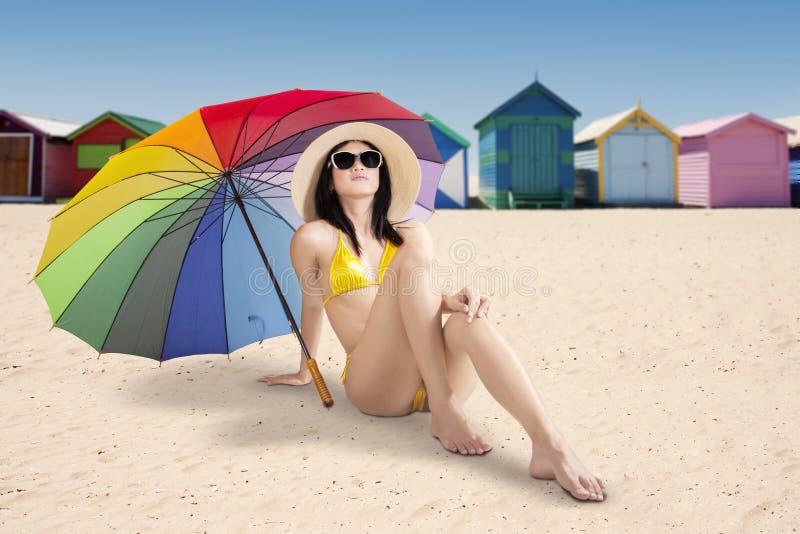Jolie femme s'asseyant à la plage de Brighton images libres de droits