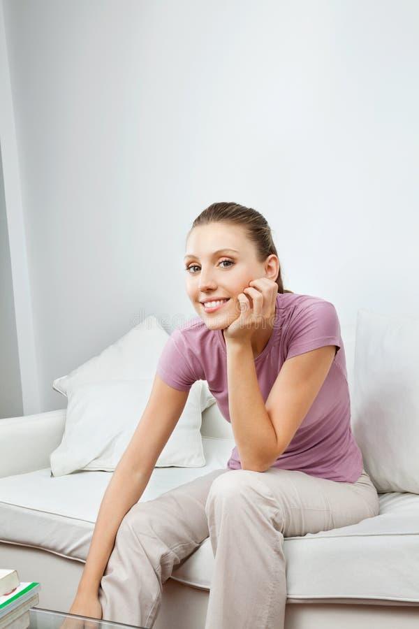 Jolie femme s'asseyant sur le sofa photographie stock libre de droits