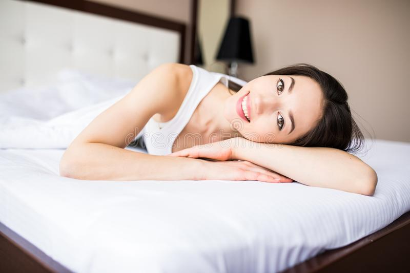 Jolie femme se couchant sur son lit à la maison pendant le matin photo stock