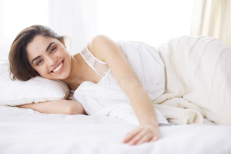 Jolie femme se couchant sur son lit ? la maison image stock