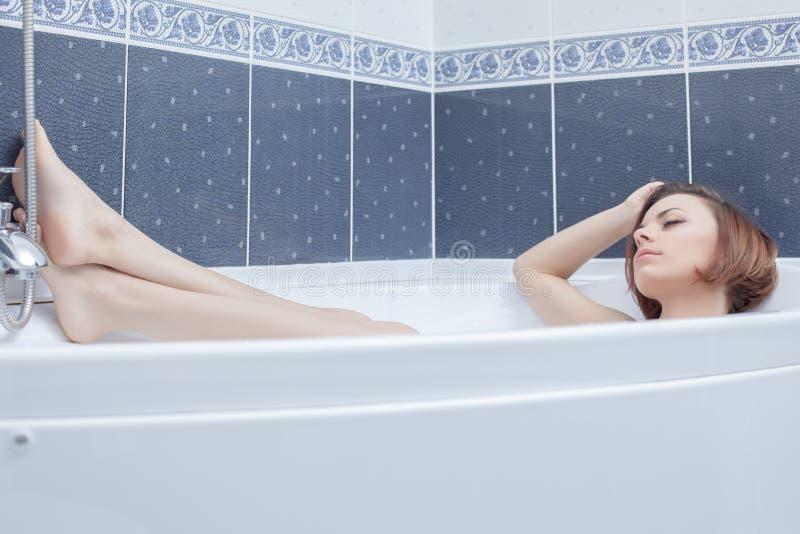 Jolie femme se situant dans le bain photos stock