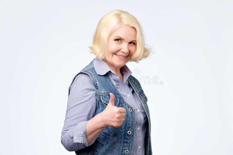 Jolie femme supérieure de sourire montrant des pouces  photos stock