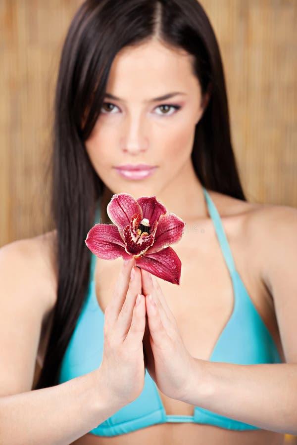 Jolie femme tenant l'orchidée photo stock