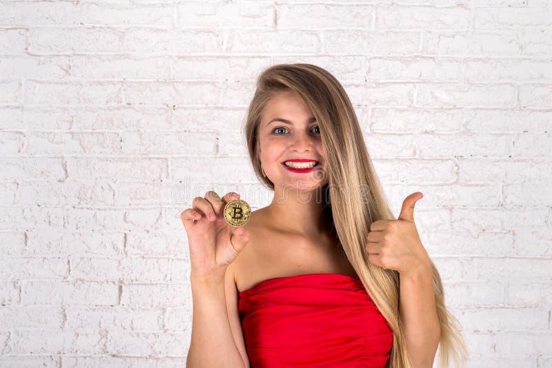 jolie femme tenant le nouveau bitcoin de cryptocurrency image stock