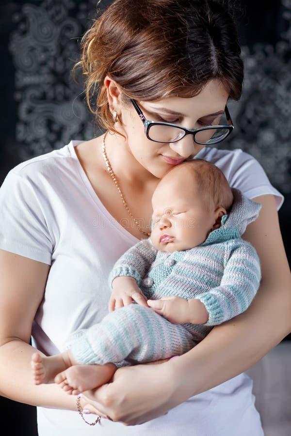 Jolie femme tenant un nouveau-né dans les bras photographie stock libre de droits