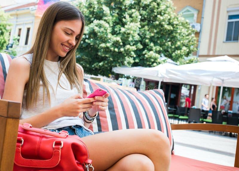 Jolie fille à l'aide du téléphone portable photographie stock libre de droits