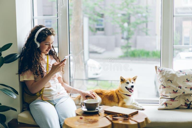 Jolie fille écoutant la musique avec des écouteurs utilisant le smartphone se reposant en café photos libres de droits