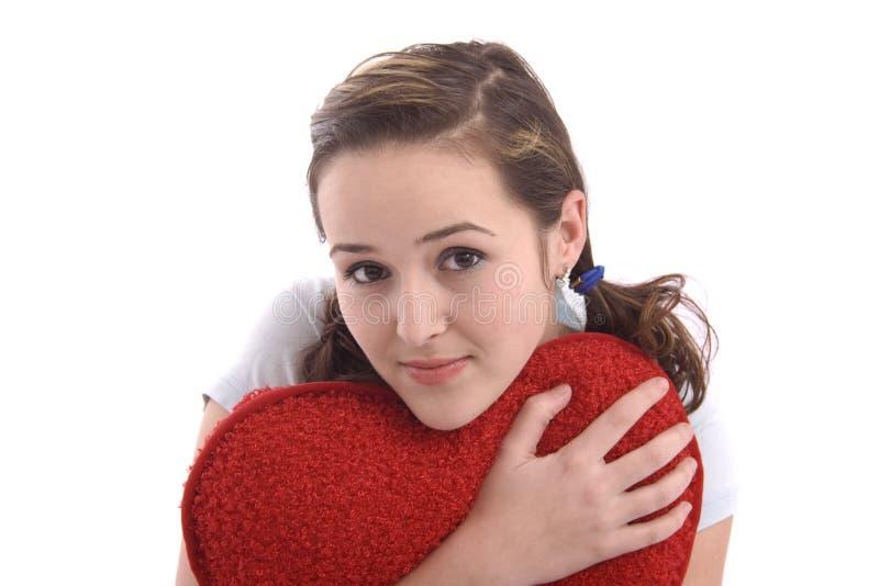 Jolie fille étreignant un grand coeur rouge de peluche photographie stock