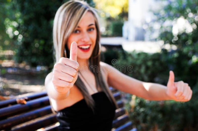 Jolie fille affichant le pouce vers le haut du signe photographie stock libre de droits