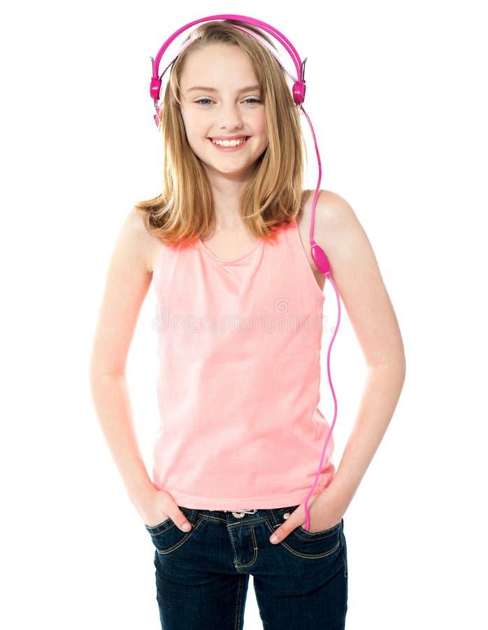 Jolie fille appréciant la musique par des écouteurs photos stock