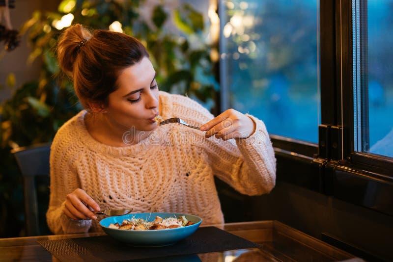 Jolie fille appréciant tout en mangeant de la salade, se reposant au café images libres de droits