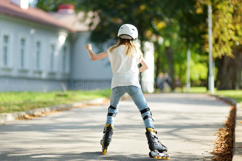 Jolie fille apprenant au patin de rouleau le beau jour d'été en parc Casque de sécurité de port d'enfant appréciant le tour de pa images libres de droits