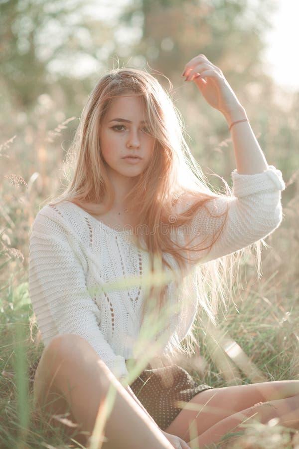 Jolie fille assise dans le champ et regardant droit dans la caméra image stock
