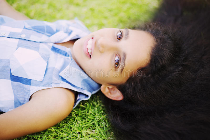 Jolie fille avec de longs cheveux de brune se trouvant sur l'herbe verte photographie stock