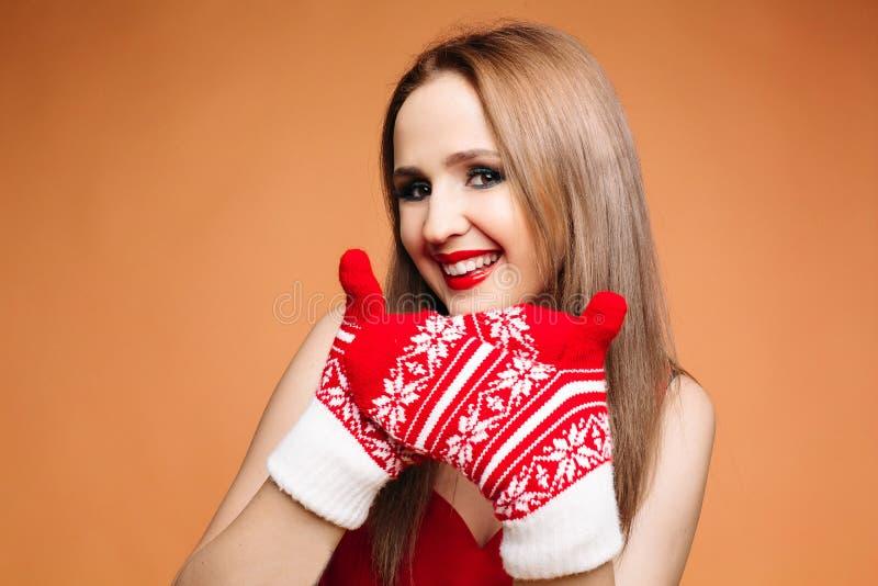 Jolie fille avec des mitaines d'hiver Portrait de studio de belle fille de brune avec le maquillage lumineux dans des mitaines or photo libre de droits