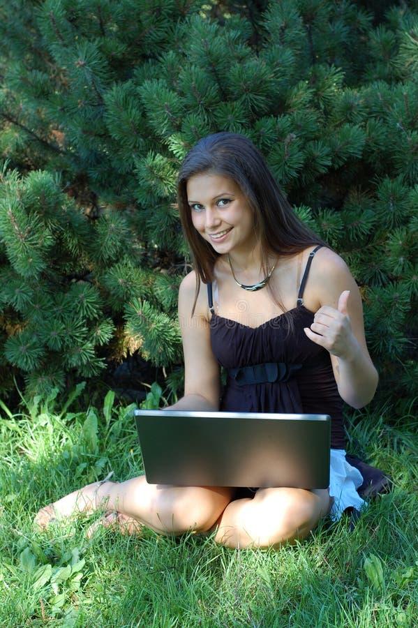 Jolie fille avec l'ordinateur portatif image libre de droits