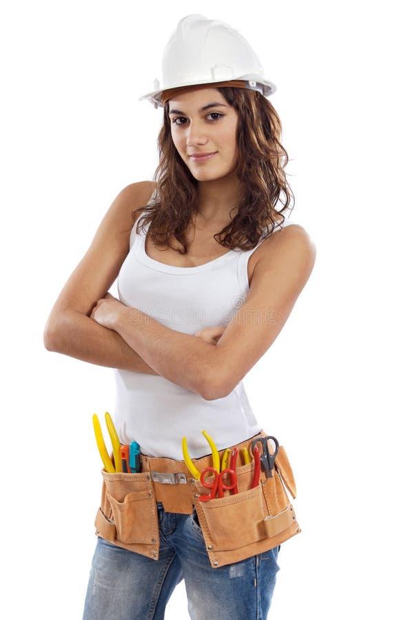 Jolie fille avec le casque et courroie des outils images stock