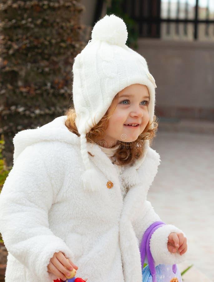 Jolie fille avec le chapeau de laine et et le manteau blanc images libres de droits