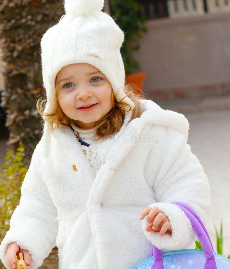 Jolie fille avec le chapeau de laine et et le manteau blanc photo libre de droits
