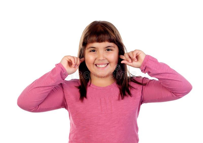 Jolie fille avec le T-shirt rose couvrant ses oreilles image stock