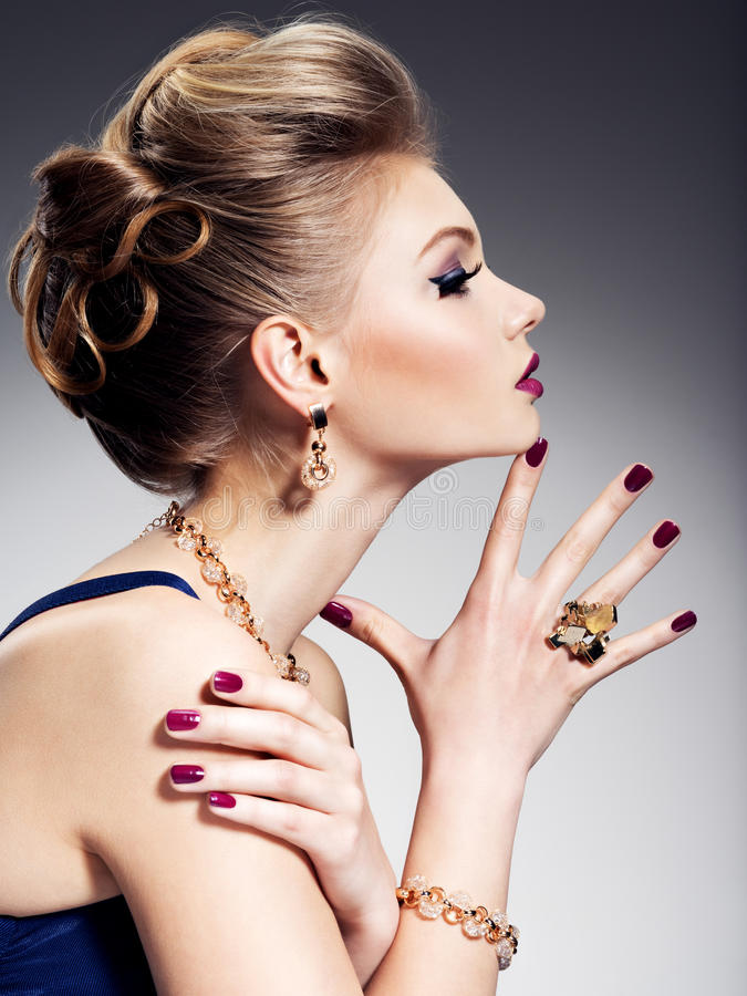 Jolie fille avec les beaux bijoux de coiffure et d'or, m lumineux image stock