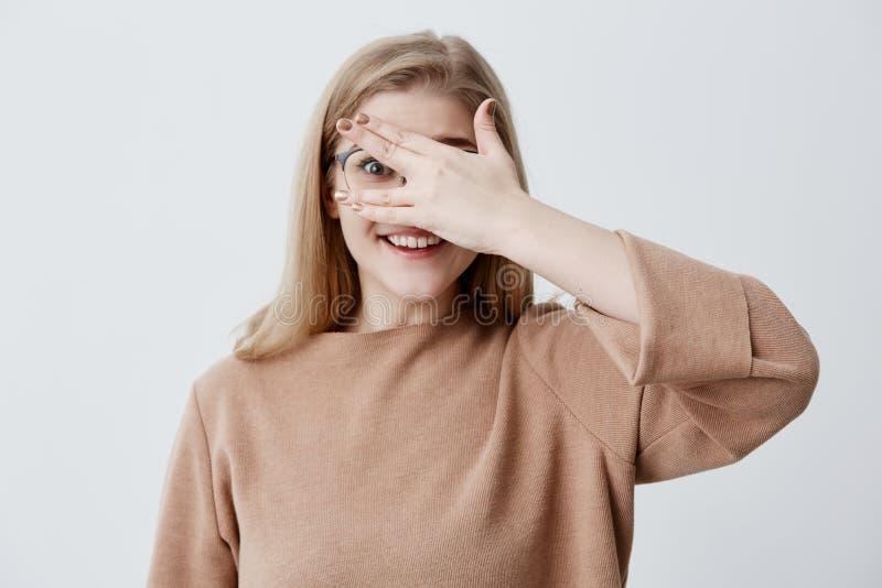 Jolie fille ayant le sembler timide jetant un coup d'oeil par ses doigts démontrant ses dents même blanches Jeune mignon gêné photographie stock