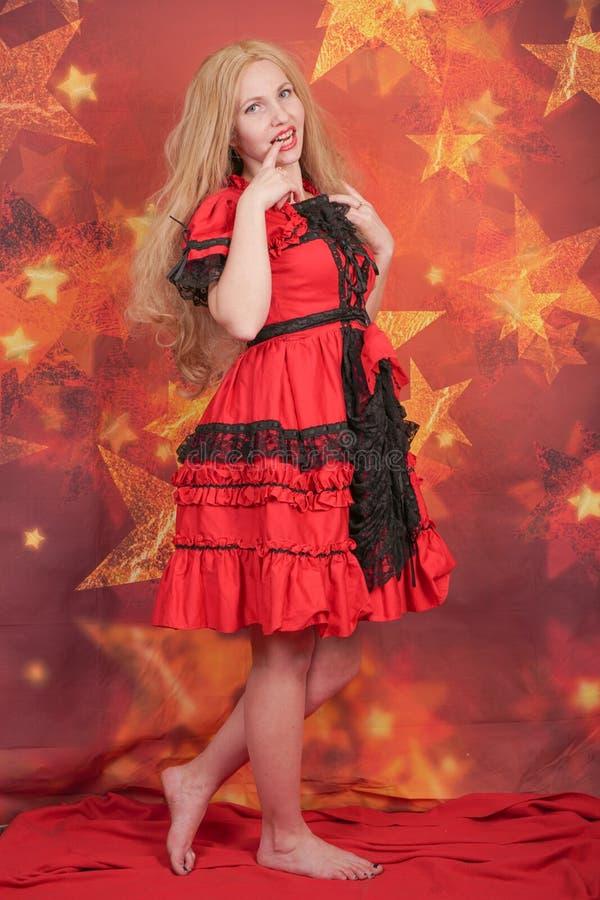 jolie fille blonde dans la position rouge de robe de conte de fées sur le fond orange avec des étoiles photographie stock libre de droits