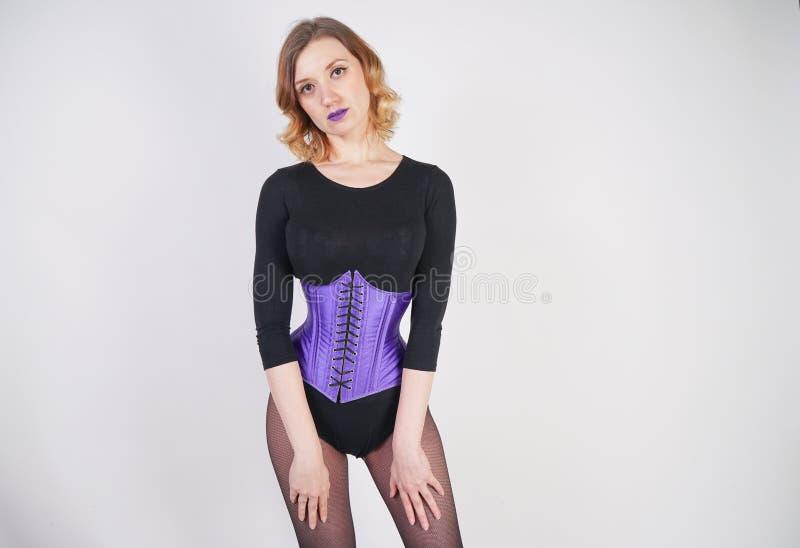 Jolie fille blonde ? la mode utilisant la salopette noire avec le collant de maille et le corset pourpre sur le fond blanc photos libres de droits