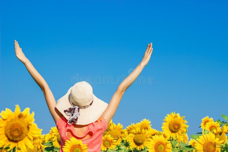 Jolie fille bouclée dans le chapeau ayant l'amusement dans le domaine des tournesols jaunes images stock