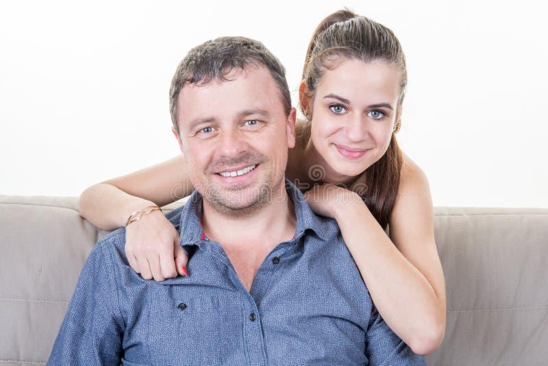 Jolie fille d'adolescent s'asseyant sur le sofa avec le père photo stock