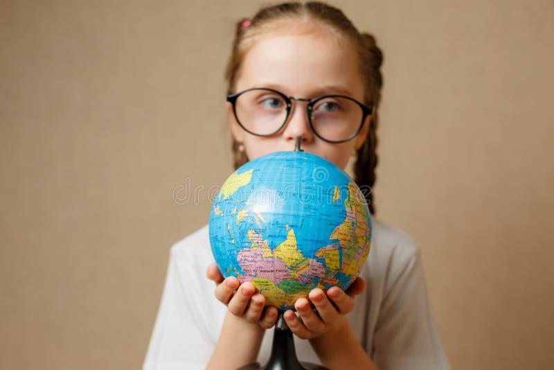 Jolie fille d'enfant avec des verres à la maison rêvant du voyage et à photographie stock libre de droits