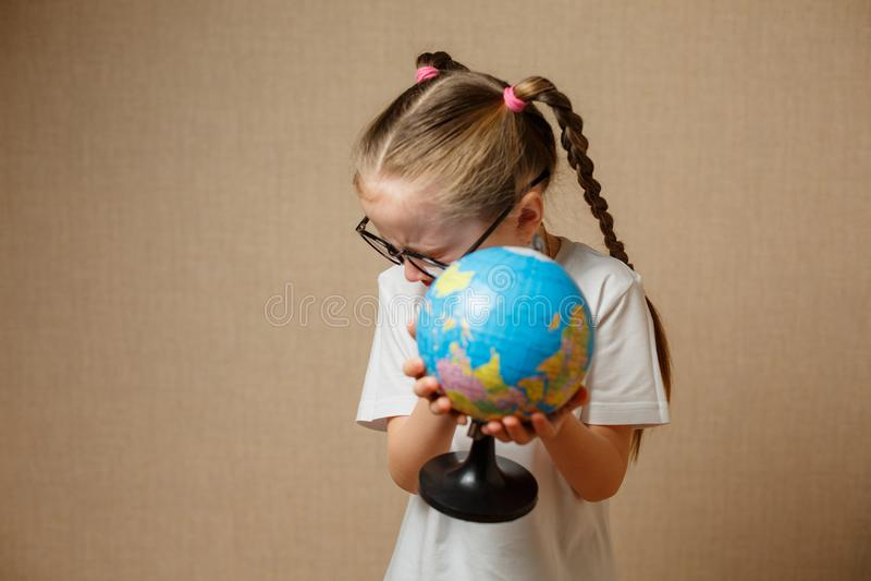 Jolie fille d'enfant avec des verres à la maison rêvant du voyage et à images stock