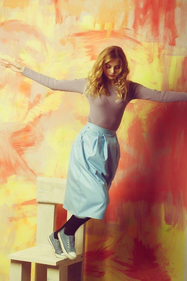 Jolie fille dans la jupe et des espadrilles bleues sur la chaise en bois photo libre de droits