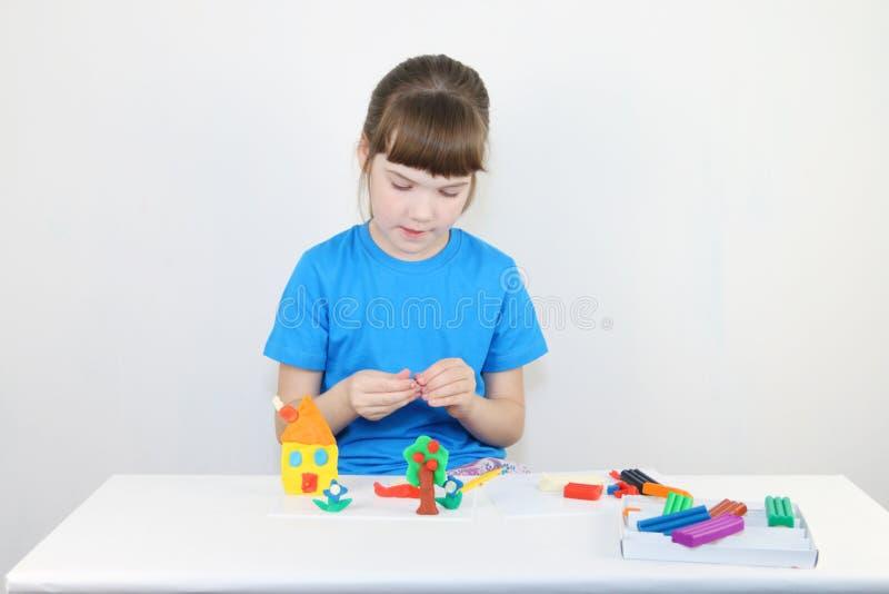 Jolie fille dans la maison de moules bleus de la pâte à modeler photos libres de droits